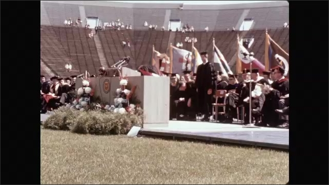 """1960s: Building.  Sign reads """"This SPACE reserved for our CONGRATULATIONS TO UM ALUMNI MCDIVITT and WHITE.""""  Graduation.  Men stand.  Man places awards on podium."""