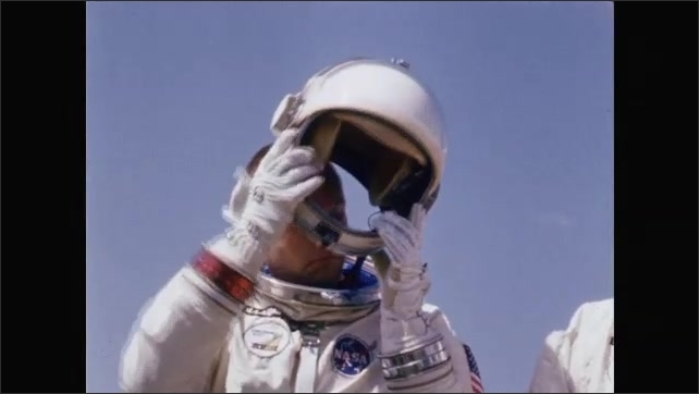 1960s: Astronauts stand in front of satellite dish.  Man takes off helmet.