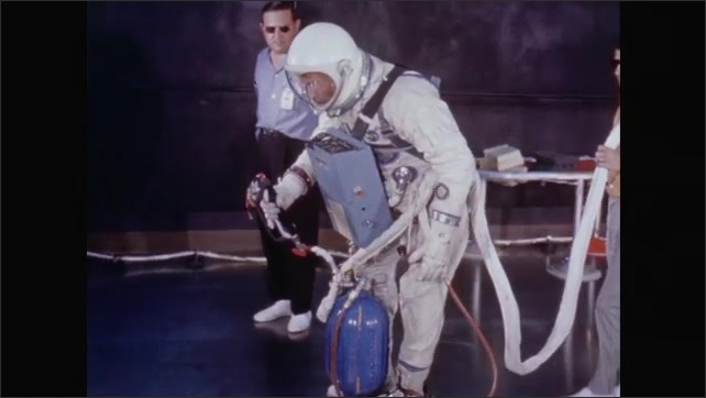1960s: Astronauts test machines while scientists watch and discuss.