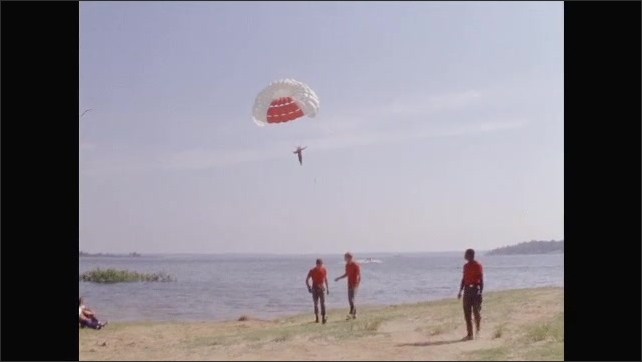 1960s: UNITED STATES: man paraglides from beach. Man flies over coast. Bonito Lava Flow field research. Geology field trip