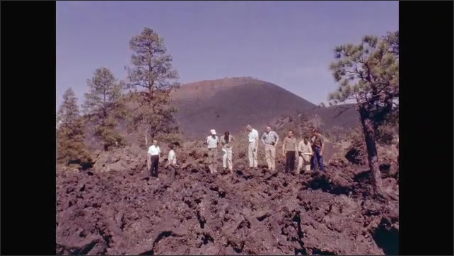 1960s: UNITED STATES: astronauts on geology field trip by lava flow. Man looks at rocks in field.