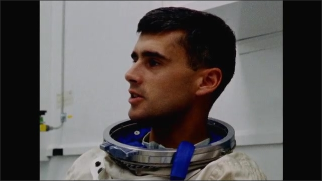 1960s: UNITED STATES: astronauts sit around in space sits in lab and chat. Man in space suit. Astronaut laughs.