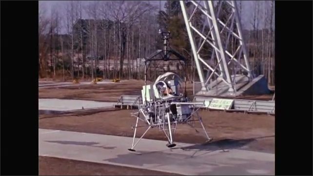 1960s: UNITED STATES: module attached to wires and tower. Learning to fly the module above the ground