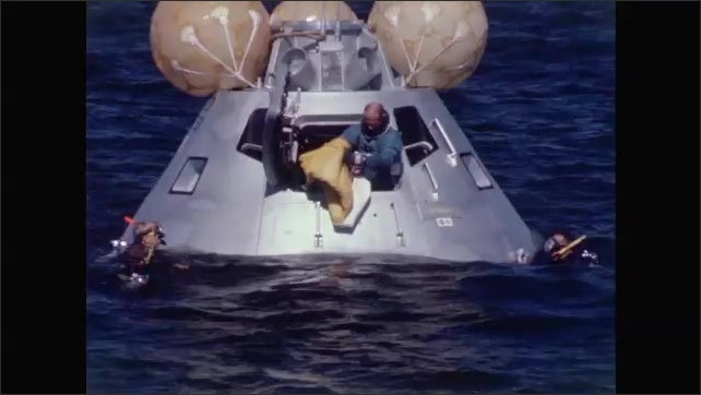 1960s: Astronaut stands in door of spacecraft as it floats in ocean and two men in scuba gear swim on either side.