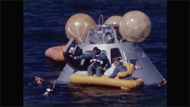 1960s: Two astronauts exit spacecraft as it floats in ocean, into small boat, as three men in scuba gear swim on all sides, assisting.