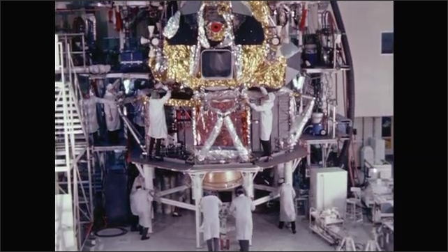 1960s: Two halves of lunar module are positioned together inside NASA factory warehouse. Engineers work on lunar module in factory building.