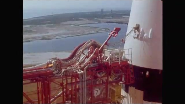 1960s: NASA rocket sits on launch pad, then explosion from rockets occurs. Clamps on rocket are released as it begins to blastoff.