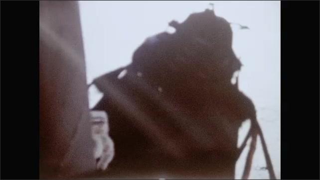 1960s: Astronaut climbs down ramp of lunar module on surface of moon.