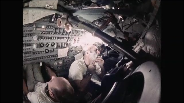 1960s: Astronaut shaves inside space capsule. Astronaut works at controls.