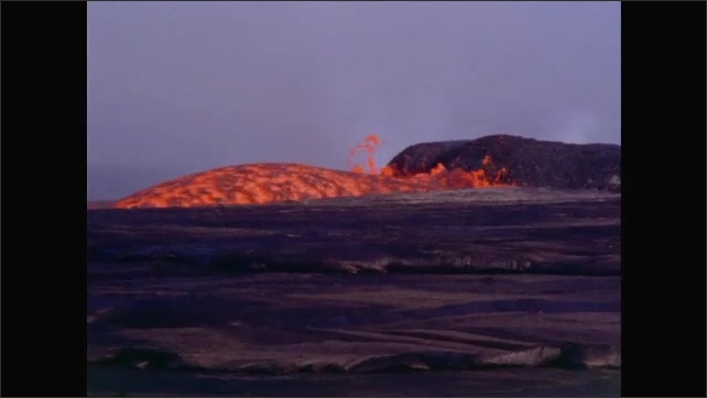 1960s: Volcanic activity. Men stand in semicircle as man crouches on ground.