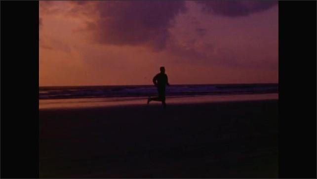 1960s: Man runs on beach.