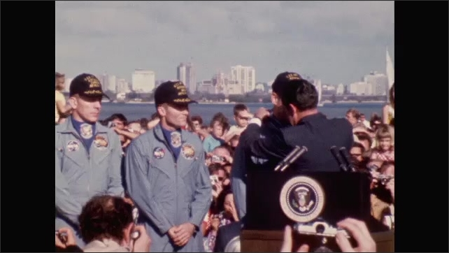 1960s: Men in uniform stand next to President Richard Nixon. President Richard Nixon places medal around neck of each man.