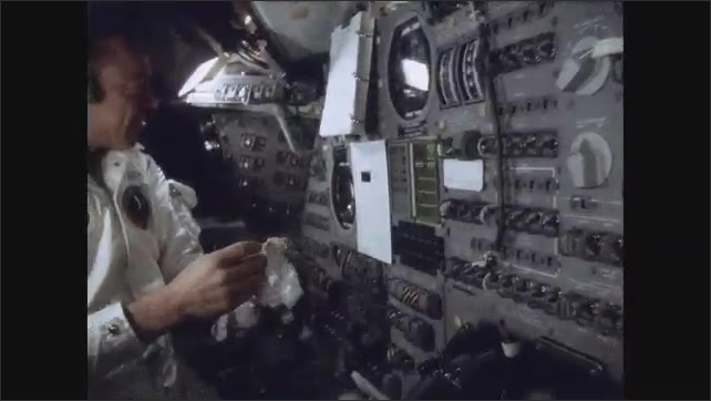 1960s: Astronaut in space smiles and floats object toward camera. Hand grasps object. Astronaut holds hands out in front of him in negative gesture. Astronaut holds object.