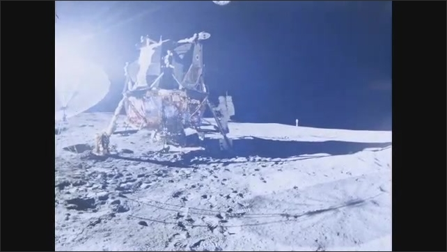 1960s: Spacecraft on surface of moon. Astronaut climbs down ladder onto surface of moon.