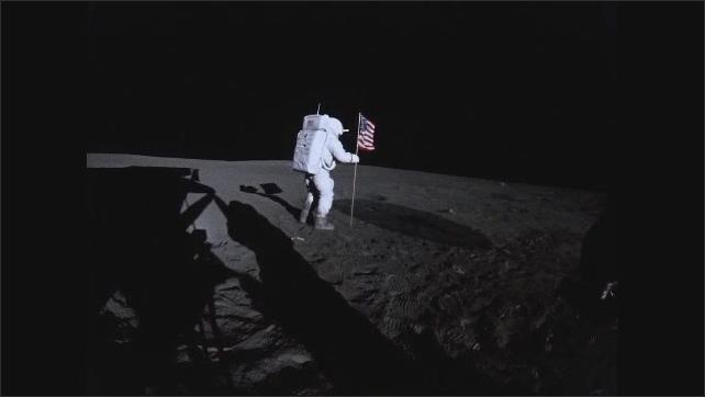 1960s: Astronaut on moon adjusts American flag.  Man runs across moon.  Men adjust camera.