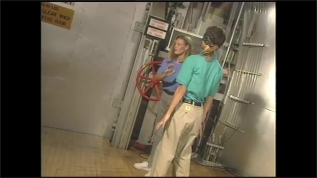 1990s: Girl leads blindfolded boy across NASA campus. Girl leads blindfolded boy into lab and speaks. Heavy door lowers. Boy removes blindfold. Man leaps over heavy door and enters lab.