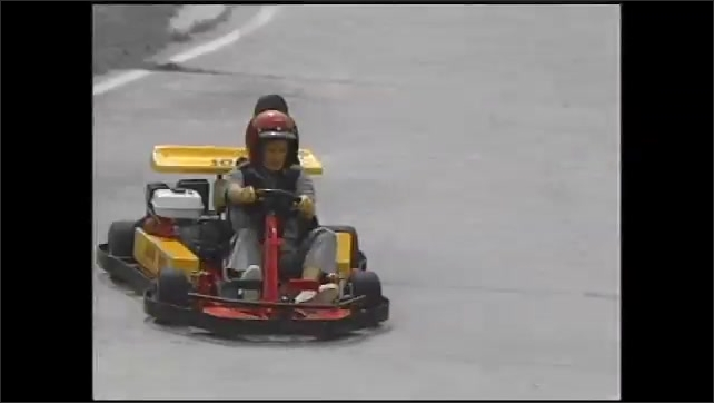1990s: Boy drives go cart and speaks. Go carts race around track. Boy stands at finish line. Girl drives cart across finish line and speaks.