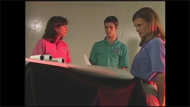 1990s: Stealth bomber flies over mountains. Woman speaks to teens near model aircraft. Girl responds to engineer.