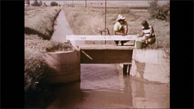 1970s: Man lowers bucket into canal to collect water sample. Man stands next to ditch with rapidly flowing drain pipe, holds up flask.