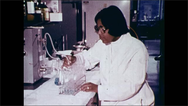 1970s: Bottle spinning. Lab equipment spins. Gun emits gas. Views of scientists in lab. Liquid in test tubes. Views of scientists in lab. Close ups of equipment. Tracking shot, entering factory.