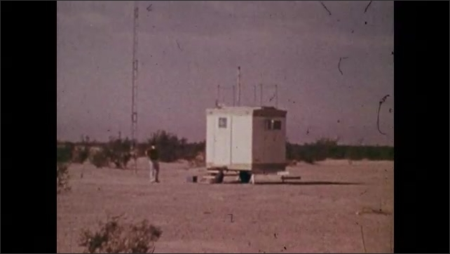 1970s: Man next to equipment. Close up of man. Close up of gauge, pan to readout Zoom in, man next to station.  View of sign, zoom out to man on roof of station.