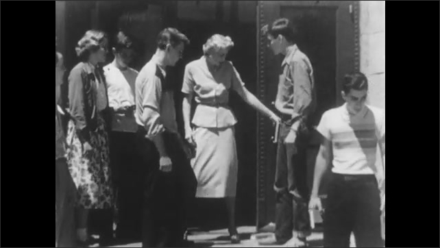 1950s: Student runs against another, knocks down his books. Student grabs student, points to floor, they push each other and fight. Woman comes out, speaks. Students take their books and leave.