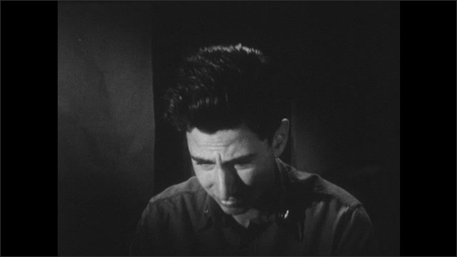 1950s: A young man sits in the dark and looks around the room, moves his head and looks down. He looks sad and regretful.