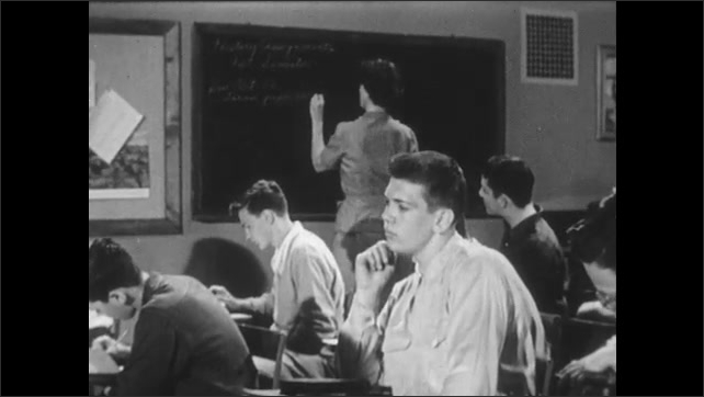 1950s: Teacher writes on blackboard, the class writes in their notebooks. One student with his hand on his chin is lost. He looks at the blackboard.