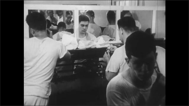 1950s: UNITED STATES: men sit in mess hall. Man eats food. Men sit at table for meal. Men shave in front of mirrors. Sailors wash.