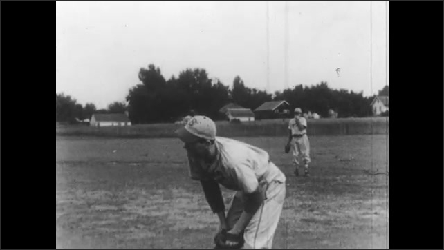 1950s: UNITED STATES: man stands in corridor. Man plays baseball. Students at baseball practice. Man catches ball.