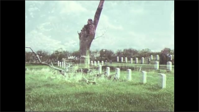 1970s: Tombstones in Gettysburg National Cemetery. Cannon overlooking battlefield.