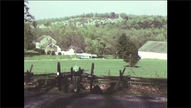 1970s: Military equipment overlooking hill at Gettysburg. Monuments on battlefield.
