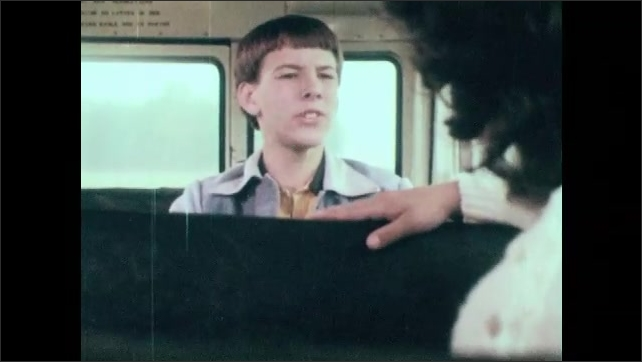 1980s: UNITED STATES: girl talks to boy on school bus. Side view of students on bus.