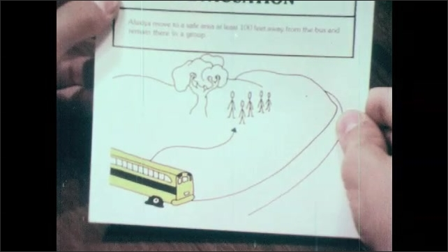 1980s: UNITED STATES: After Evacuation title. Boy reads bus evacuation leaflet