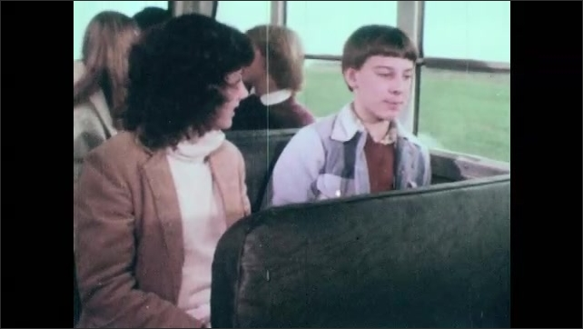 1980s: UNITED STATES: boy rides home from school on bus. Boy talks to girl on bus