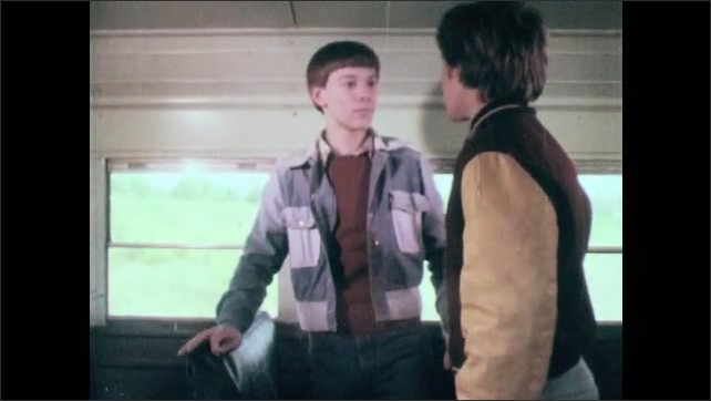 1980s: UNITED STATES: boy takes first aid kit from boy. Students evacuate bus after crash