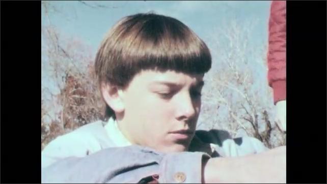 1980s: UNITED STATES: boy sits on ground. Boy feels sad. Students talk to boy on ground
