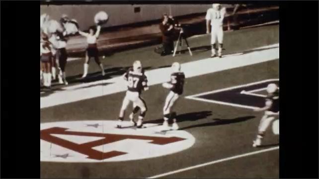 1970s: Football game.  Player scores touchdown.  Crowd cheers.  Stadium.