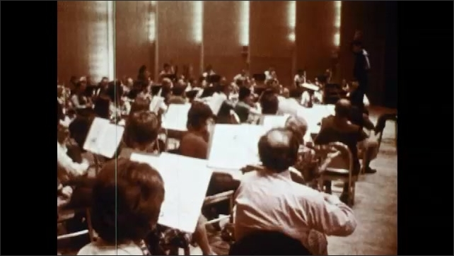 1970s: Theater.  People enter building.  Orchestra plays.  Man conducts.