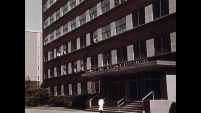 """1970s: Building is labelled as """"THE BUFFALO GENERAL HOSPITAL.""""  Man walks past building."""