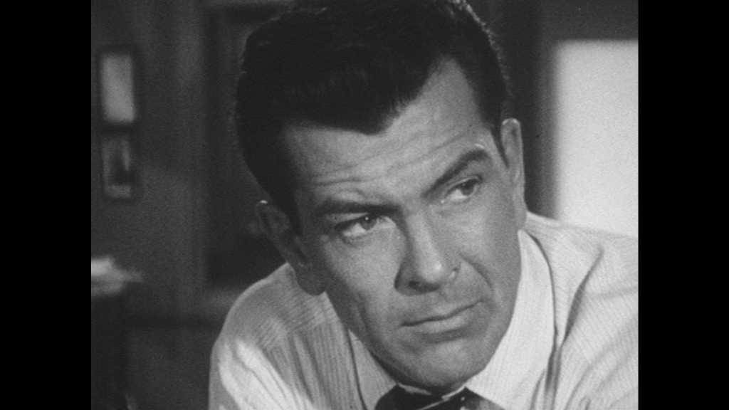 1950s: Office.  Man raises eyebrows and speaks.