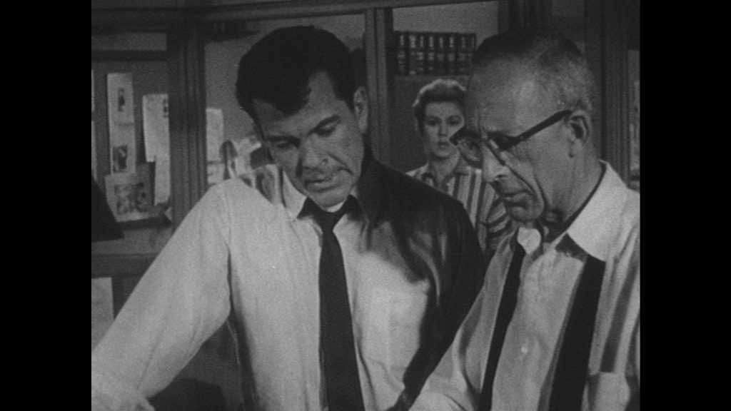 1950s: UNITED STATES: men talk in office. Lady stands in office doorway. Man wipes face with hand. Man leaves room. Man grabs jacket from stand