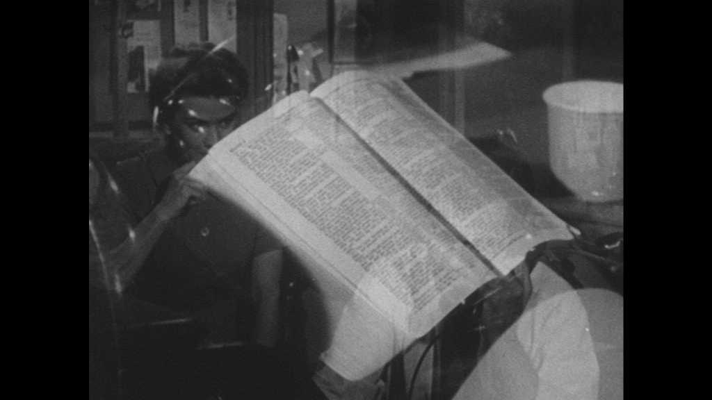 1950s: UNITED STATES: Bible on table. Bible and mug on desk. Typewriter slides sideways. Man drinks coffee. Highway Bypass Voted In headline on newspaper