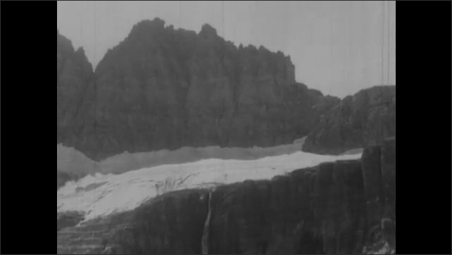 1950s: Mountains.  Glacier.  People ride horses on path.  Men look down into crevasse.