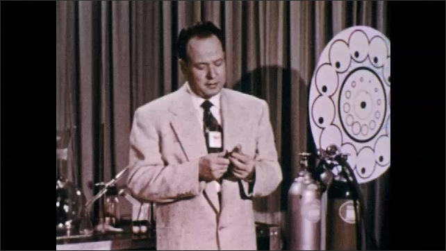 1960s: UNITED STATES: presenter speaks to camera. Man puts down lamp. Man picks up photo cell. Man walks across studio.