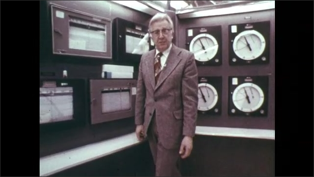 1970s: Man looks through portal and turns wheel.  Man walks and talks near wall of gauges.  Man holds up pages of graphs.