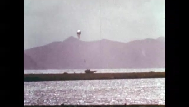 1970s: Man launches weather balloons.  Boat on water.  Buoy is taken from water.  Men operate machinery.