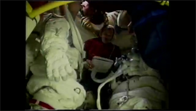 1990s: Astronaut is suspended on arm above Space Shuttle bay. Astronauts at work in spacesuits in space. Man in Space Shuttle looks at chart. Man assists woman into space suit.