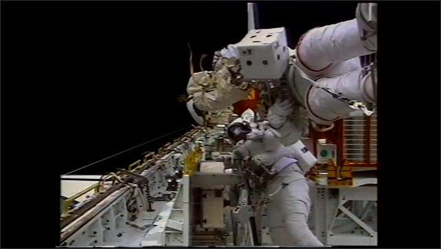 1990s: Astronaut in spacesuit in space uses drill to repair satellite. Astronauts floating in Space Shuttle bay. Animation concept of space station.