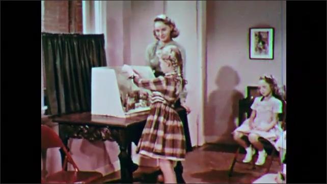 1950s: Little girl arranges nativity scene.  Woman speaks.  Little girls sit.